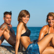 Stock Photo: Group portrait of threesome on beach.