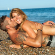 Sexy couple laying on pebble beach. — Stock Photo #12792795