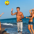 Three friends playing with ball on beach. — Стоковая фотография