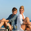 Two attractive girls sitting back to back on beach. — Stock Photo #12792851
