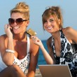 Two girlfriends shopping on line at beach. — Foto de Stock