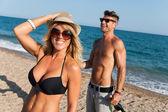 Couple enjoying afternoon sun on beach. — Stock Photo