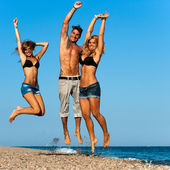 Energetic friends jumping on beach. — Stock Photo