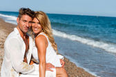 Handsome couple in white on beach. — Stock Photo