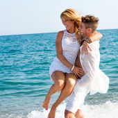 Happy couple playing in waves. — Stock Photo