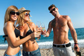 Tree attractive friends making a toast on the beach. — Stock Photo