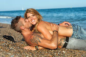 Sexy couple laying on pebble beach. — Stock Photo