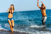 Young attractive couple splashing water at sea side. — Stock Photo