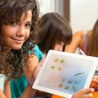 Cute girl showing homework on tablet. — Stock Photo #13137529