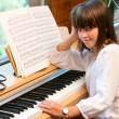 Portrait of cute little girl at piano. - Stock Photo