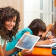 Stock Photo: Young girl showing homework on tablet indoors.