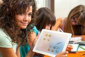 Leuk meisje tonen huiswerk op tablet pc. — Stockfoto