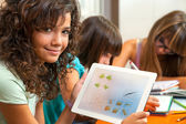 Cute girl showing homework on tablet. — Stock Photo
