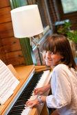 Cute little girl playing piano. — Stock Photo