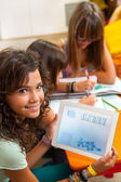Young girl holding tablet with schoolwork. — Stock Photo