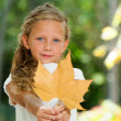 Close up portrait of sweet girl holding dry leaf. — Stock Photo