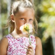 Blue eyed girl hiding behind flower. — Stock Photo #13251697