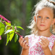 Cute girl outdoors picking berries. — Stock Photo