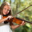 Cute girl in white playing violin outdoors. - Stock Photo