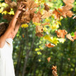 Girl playing with autumn leaves outdoors. - Stock Photo
