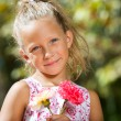 Sweet girl holding flowers outdoors. - Stockfoto