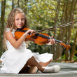 Young girl playing violin in the woods. - Stock Photo