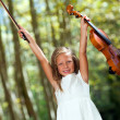 Happy violinist raising violin outdoors. - Stock Photo