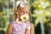 Blue eyed girl hiding behind flower. — Stock Photo