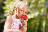 Blue eyed girl smelling flower outdoors. — Stock Photo