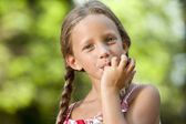 Cute girl licking off chocolate fingers. — Stock Photo