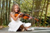 Young girl playing violin in the woods. — Stock Photo