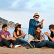 Group of friends singing on beach. — Stok fotoğraf #13535737