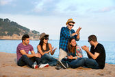 Group of friends singing on beach. — Stock fotografie