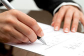 Female hand with pen pointing on accounting document. — Stock Photo