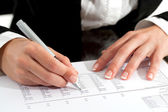 Female hands with pen reviewing document. — Stock Photo