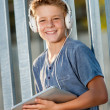 Cute teen boy holding tablet outdoors. - Stock Photo