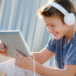 Cute teen boy with headphones and tablet. — Stock Photo #13654588