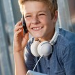 Stock Photo: Portrait of smiling boy talking on smart phone.