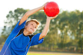 Young boy catching red ball outdoors. — Stock Photo