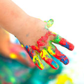Colorful painted infant hand. — Stock Photo