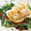 Grilled cod fish with spinach leaves. - Stock Photo