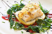 Grilled cod fish with spinach leaves. — Stock Photo