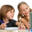 Cute girl showing classmate homework on tablet. — Stock Photo #14180288