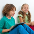 Two kids sitting with laptop and digital tablet. — Stock Photo