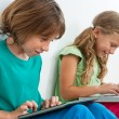 Stock Photo: Two kids playing on tablet and laptop.