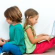 Two kids socializing with laptop and tablet. — Stock Photo