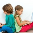 Stock Photo: Two kids socializing with laptop and tablet.