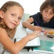 Stock Photo: Young kids doing schoolwork together at desk.