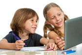 Cute girl showing classmate homework on tablet. — Stock Photo