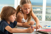 Girl helping boy with homework. — Stock Photo
